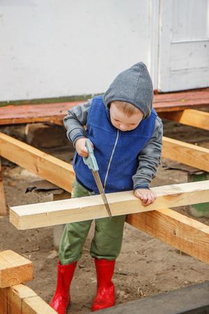 studious: Little studious boy sawing a wooden board. Home construction. Little Helper. Little builder.
