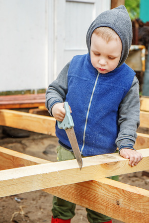 tools construction: Little studious boy sawing a wooden board. Home construction. Little Helper. Little builder.