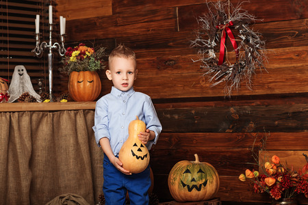 young boy smiling: Cute Little Boy having fun in Halloween decorations. Halloween party with child holding painted pumpkin