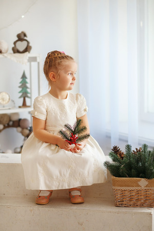 fir twig: Portrait of a cute little blonde girl holding fir twig and looking out the window in the interior with Christmas decorations. Beautiful Little girl waiting for a miracle in Christmas decorations Stock Photo