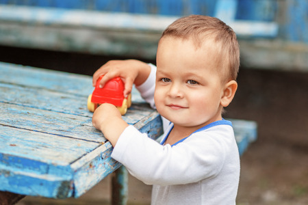 cute boys: Beautiful brown-eyed little boy playing with a red plastic toy machine outdoors Stock Photo
