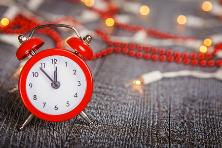 twelve month old: Christmas composition - red alarm clock on a textured wooden board with lights and beads bokeh Stock Photo
