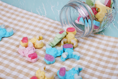 voluminous: colorful neon gummy a cow candies scattered from glass jar