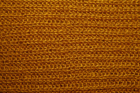 close knit: Close up on knit woolen fur texture. mustard fluffy woven thread sweater as a background.