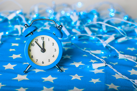 12 days of christmas: Christmas composition - blue alarm clock with lights bokeh on a blue fabric background with stars ornament Stock Photo