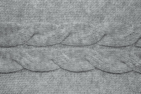Wool sweater texture close up. Knitted jersey background with a relief pattern. Braids in machine knitting pattern