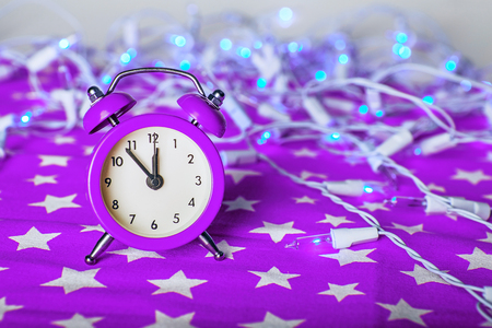 12 month old: Christmas composition - lilac, violet, purple alarm clock with lights bokeh on a fabric background with stars ornament