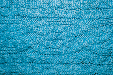 Wool sweater or scarf texture close up. Knitted jersey background with a relief pattern. Braids in machine knitting pattern. Wool hand-knitted or machine knitting pattern. Closeup Fabric Background