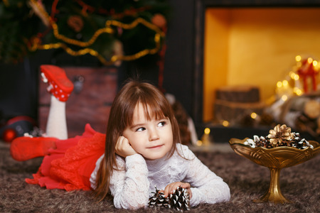 Beautiful Little girl waiting for a miracle in Christmas decorations. New year preparation