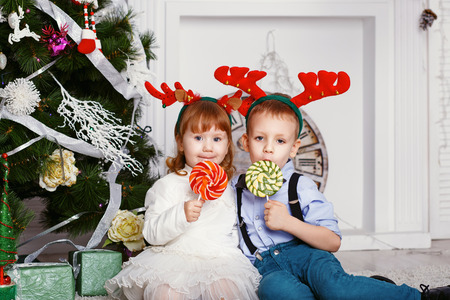 christmas toys: Little girl and boy in reindeer antlers eating a lollipops. Portrait of two funny little kids with a delicious candies in the hands. Christmas and New Year concept. Happy children and family In anticipation of the new year and Christmas.