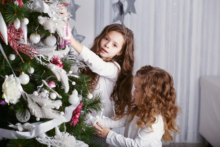 Little girls in comfortable home clothes in beautiful Christmas decorations. Two little sisters decorating Christmas tree with toys and balls. New year preparation. Happy girls and family.