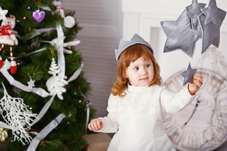 corona navidad: Retrato de una hermosa ni�a en un vestido blanco y una corona en el interior con decoraciones de Navidad. La peque�a princesa que juega con el juguete estrellas - Decoraciones de Navidad Foto de archivo