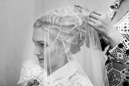 get dressed: Mother helping young beautiful bride to get dressed for the wedding ceremony. Black and white photography
