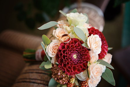 Great bridal bouquet of roses, peonies, dahlias, asters and dried flowers. Gold wedding rings on a bouquet