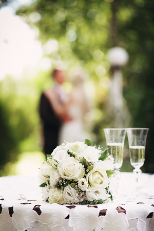 Wedding bridal bouquet with white roses on the table in the garden against the background of the bride and groom. Wedding concept