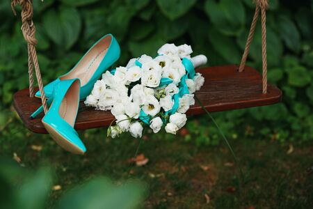 patent leather: Attributes runaway bride. Wedding bouquet of white roses and blue ribbons and blue patent leather high-heeled shoes