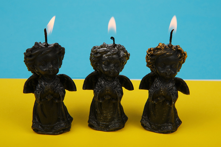 annexation: Candles in the form of black  praying angels on background Ukrainian flag to honor those who perished in war in Ukraine. Candles black angel symbolize the war in Ukraine. Pray for Ukraine. Stop war