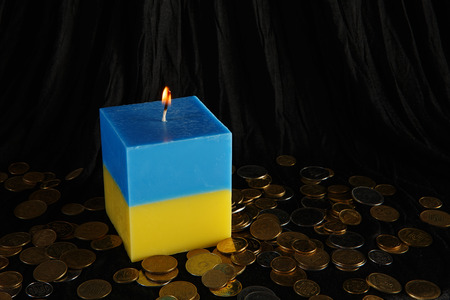 damnation: Candle blue and yellow as a symbol of Ukraine. Inflation in Ukraine. Ukrainian depreciating coins Stock Photo