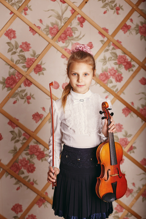 Portrait of the little violinist. Beautiful gifted little girl playing on violin against the background of wallpaper with floral patterns and wooden lattice. Shabby chic decor