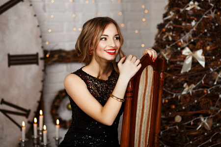 Portrait of a beautiful long-haired young girl in black Evening Dress in interior with Christmas decorations