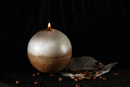 metier: Decorative Handmade sphere candle. Candlelight. Beautiful handmade candle on cloth background Stock Photo