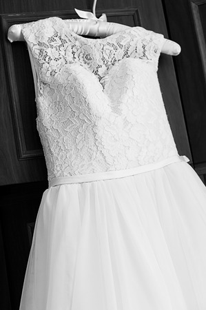 soft tissue: Wedding dress hanging on on the soft tissue hanger. Beautiful female wedding dress with upper part of lace. Black and white photography Stock Photo