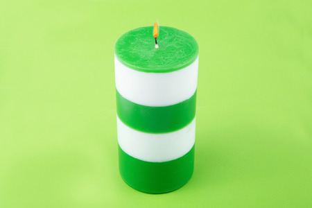 cylindrical: White and green striped cylindrical handmade candle. Light the candles. A burning candle. Candle lit. Candle Light