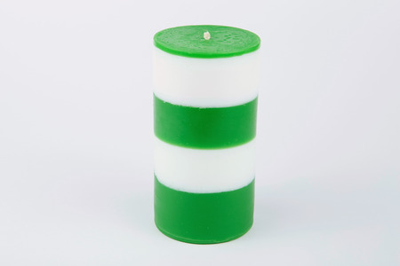 cylindrical: White and green striped cylindrical handmade candle on white background Stock Photo