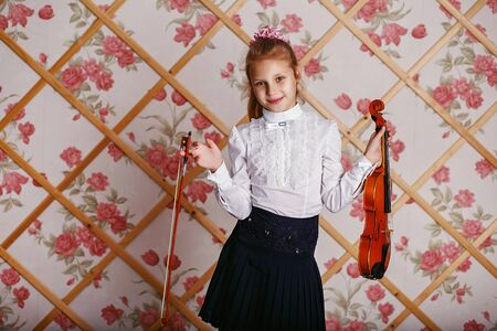Beautiful gifted little girl playing on violin against the background of wallpaper with floral patterns and wooden lattice. Shabby chic decor Stock Photo