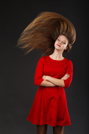 waver: Portrait of a smiling young beautiful girl in a red dress with a flying hair. Girl with long flowing hair. Hair fluttering in motion.