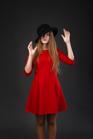 A beautiful girl in red dress and black felt hat.