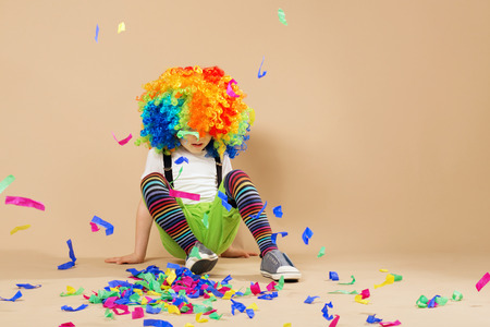 trumpery: Happy clown boy with large colorful wig. Little boy in clown wig jumping and having fun. Portrait of a child throws up a multi-colored tinsel and confetti. Birthday boy.