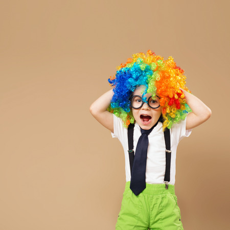 blithe: Blithesome children. Happy clown boy with large colorful wig. Close-up Portrait of Little boy in clown wig and eyeglasses