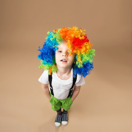 frippery: Happy clown boy with large colorful wig. Little boy in clown wig jumping and having fun. Portrait of a child shot on a wide-angle lens. Birthday boy. Positive emotions. Top view portrait