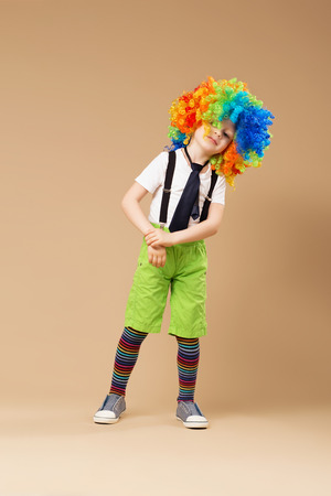 blithe: Blithesome children. Happy clown boy with large colorful wig. Little boy in clown wig dancing and having fun. Full-length portrait of Birthday boy.