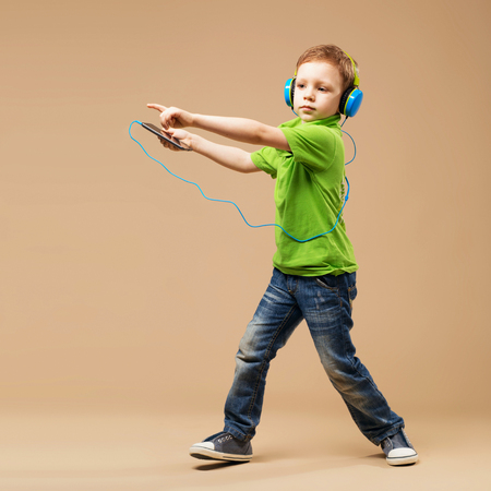 Dance! Handsome little stylish boy in headphones holding MP3 Player and dancing while standing against beige background