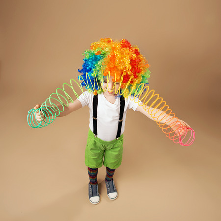 droll: Happy clown boy with large colorful wig. Little boy in clown wig playing with a spring. Portrait of a child shot on a wide-angle lens. Birthday boy. Positive emotions. Top view portrait