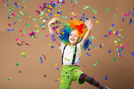trumpery: Little boy in clown wig jumping and having fun celebrating birthday. Portrait of a child throws up a multi-colored tinsel and confetti. Birthday boy. Positive emotions.