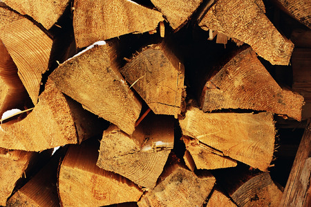 mantel: The stack of the snowy firewood on old wooden background. Wood pieces, tree chops stored outdoors for fireplace or mantel, texture or background. Stock Photo