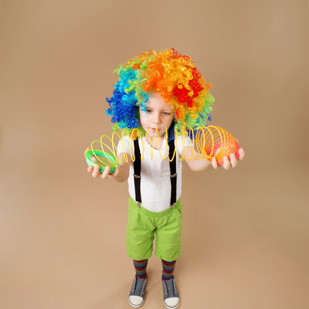 laughable: Happy clown boy with large colorful wig. Little boy in clown wig plays with a spring. Portrait of a child shot on a wide-angle lens. Birthday boy. Positive emotions. Top view portrait