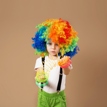 frippery: Happy clown boy with large colorful wig. Little boy in clown wig playing with a spring. Birthday boy. Positive emotions. Stock Photo