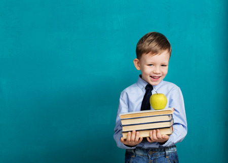 Book, school, kid. little student holding books. Cheerful smiling little kid against chalkboard. Looking at camera. School concept. Back to School