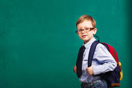 School, kid, rucksack. little Boy in eyeglasses. Cheerful smiling little kid with big backpack against chalkboard. Looking at camera. School concept. Back to School Foto de archivo