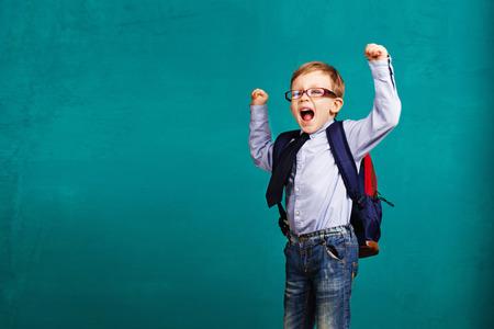 Schattig lachende kleine jongen met grote rugzak springen en plezier tegen de blauwe muur. Kijkend naar de camera. School concept. Terug naar school Stockfoto
