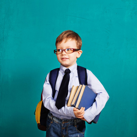 studious: Book, school, kid. Diligent, sedulous, studious student holding books. Cheerful smiling little kid with big backpack against chalkboard. Looking at camera. School concept. Back to School