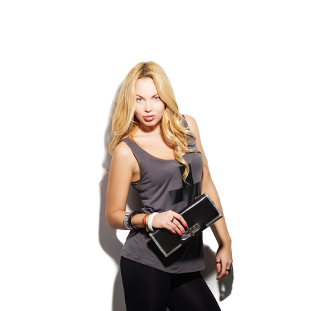 clutch bag: Fashion model girl portrait dressed in tight black pants, top and modern accessories holding clutch bag. Street fashion, casual style. Isolated on white background