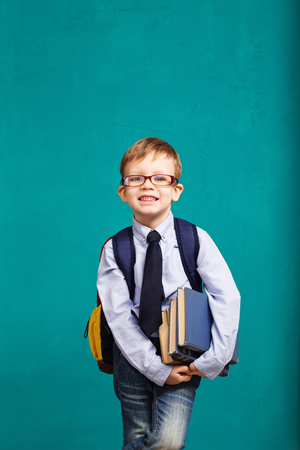 Book, school, kid. little student holding books. Cheerful smiling little kid with big backpack against chalkboard. Looking at camera. School concept. Back to School