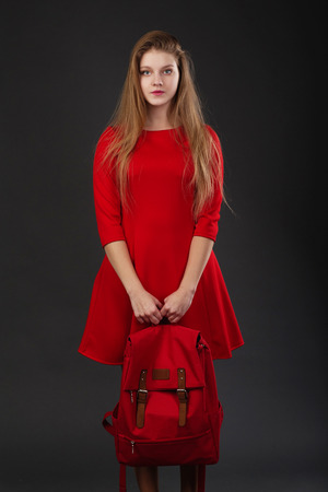 loose hair: Portrait of a girl in red dress with loose hair, with a big red backpack in hands