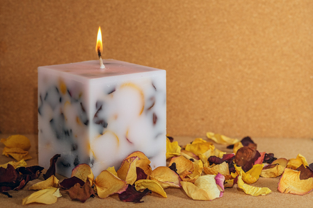 Decorative Handmade candle in the shape of a cube among dry rose petals on cork surface
