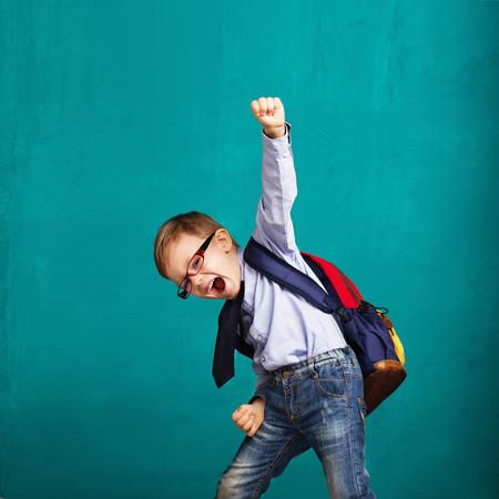 Fröhlich lächelnd kleiner Junge mit großen Rucksack springen und Spaß gegen den blauen Wand. Betrachtet man die Kamera. Schulkonzept. Zurück zur Schule